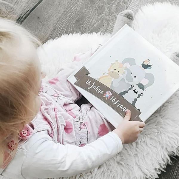 Baby-Tagebuch 18 Jahre - 18 Fragen in der Hand von einem sitzenden Mädchen